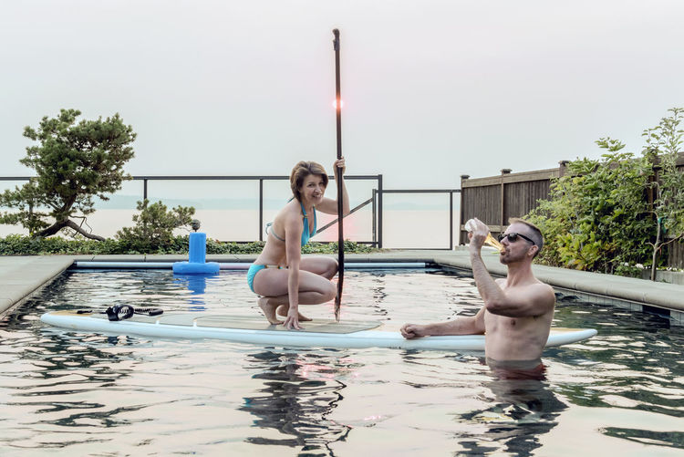 Couple in a swimming pool enjoying a beer on a hazy summer day. Architecture Beer Building Exterior Caucasian Couple Dating Day Drinking Full Length Leisure Activity Lifestyles Married Middle Aged Nature Outdoors People Real People Refreshment Relationship Shirtless Sky Swimming Pool Togetherness Water Young Adult