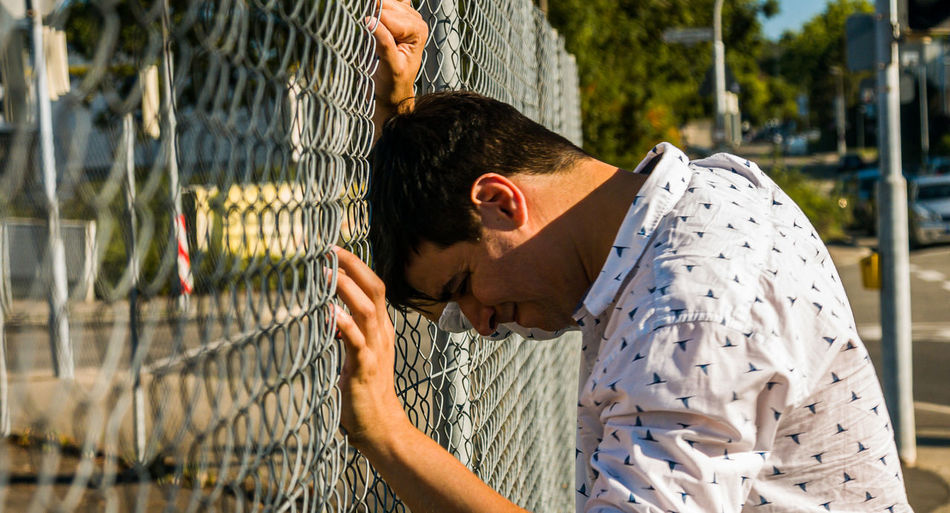 Rear view of young man standing by fence