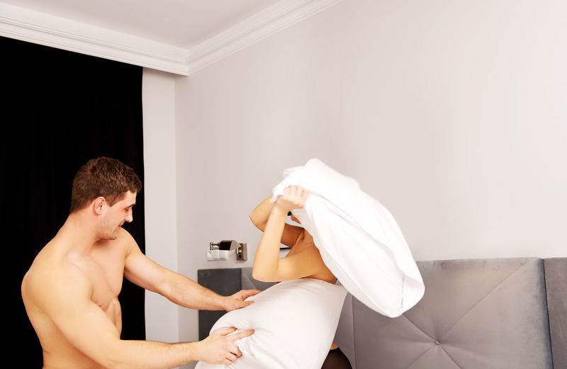 Man and woman pillow fighting at home