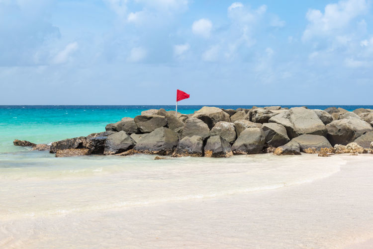 Red Warning Flag on a Beach Barbados Beauty In Nature Caribbean Caribbean Sea Danger Day Flag Horizon Over Water Nature No People Outdoors Red Flag Rock - Object Scenics Sea Sky Tranquil Scene Tranquility Warning Flag Water