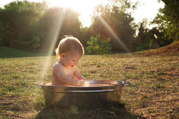 Cute little kid sits in a basin of water in nature and has rays of the setting sun, golden bathe.
