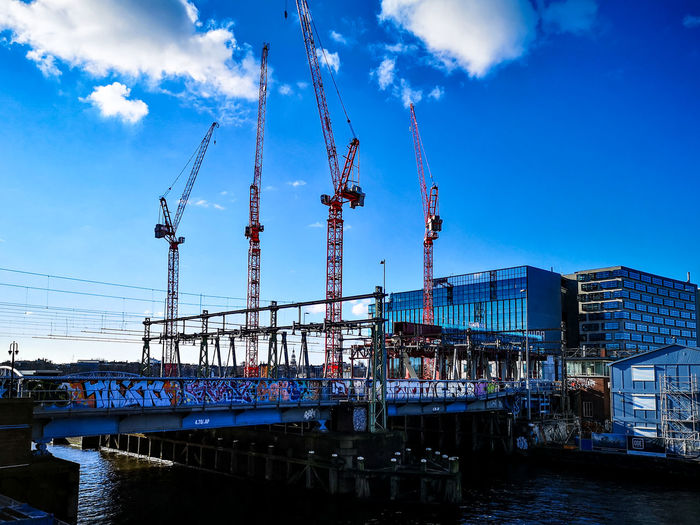 Cranes at construction site in city against sky