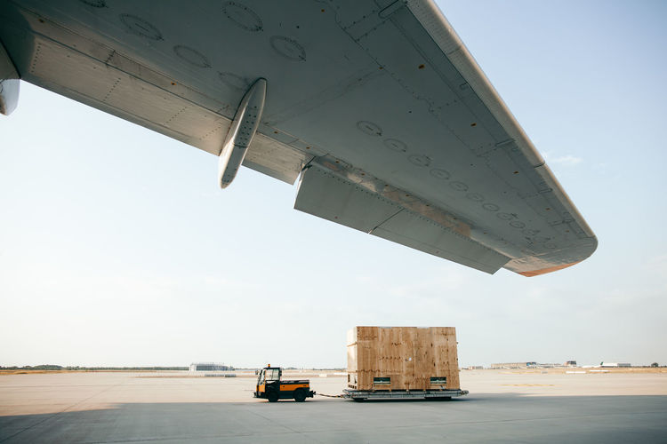 container box and wing of an airplane Economy Transportation Worker Working Air Vehicle Airplane Airport Business Cargo Cargo Aircraft Cargo Container Chains Container Export Freight Transportation Globalization Import Industry Land Vehicle Mode Of Transportation Safety Shipping  Transportation Travel Worldwide
