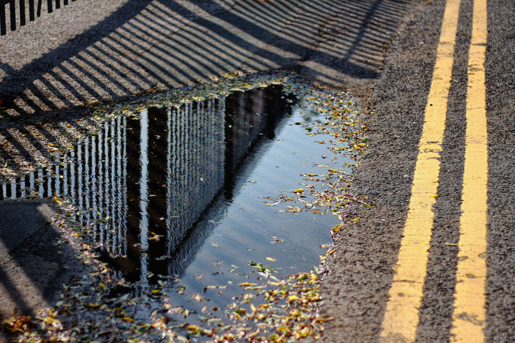 Reflection of railing in puddle on road