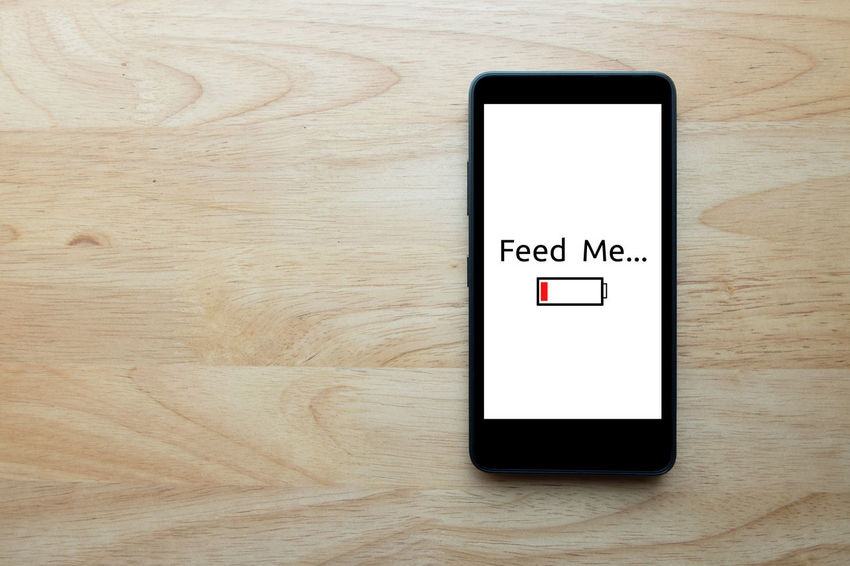 """Smart phone show text on screen """"feed me"""" status show low battery with notebook on wooden table background. Communication Digital Display Low Battery Smart Phones  Table Technology Top View Of Food Touch Screen Wireless Technology"""