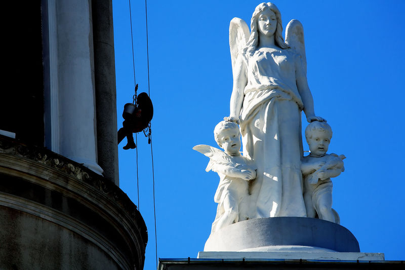 Low angle view of window washer working by angel statue against clear blue sky