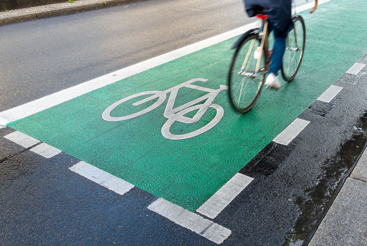 Low section of people riding bicycle on road