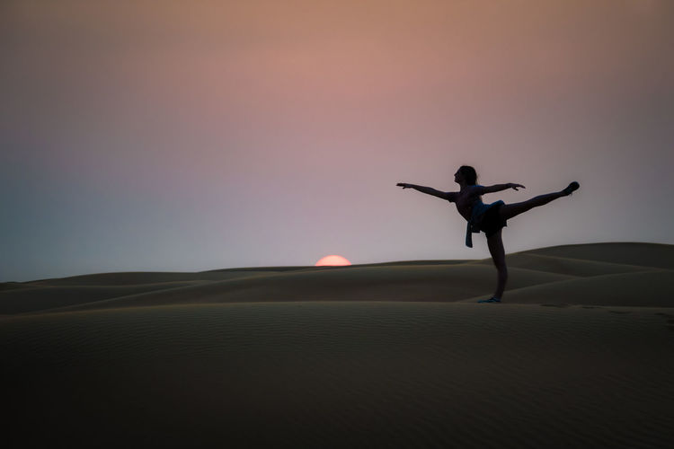 Ballet Beauty In Nature Clear Sky Dancer Day Desert Landscape Lifestyles Nature One Person Outdoors People Real People Sand Silhouette Sky Sunset Go Higher The Traveler - 2018 EyeEm Awards