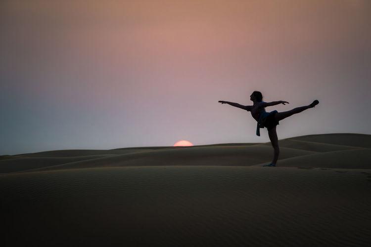 Silhouette man in desert against sky during sunset