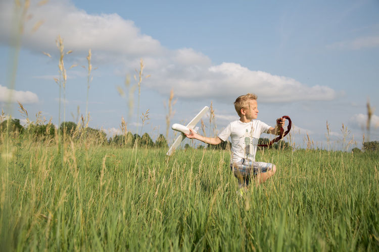 Boy running on the field playing with his toy plain Freedom Green Happy :) Running Traveling Adventure Boy Child Childhood Clouds Enjoying Life Field Journey Kid Leisure Activity Lifestyles Long Grass Nature One Person Playing Red Ribbon Sky Speed Spring Summer First Eyeem Photo