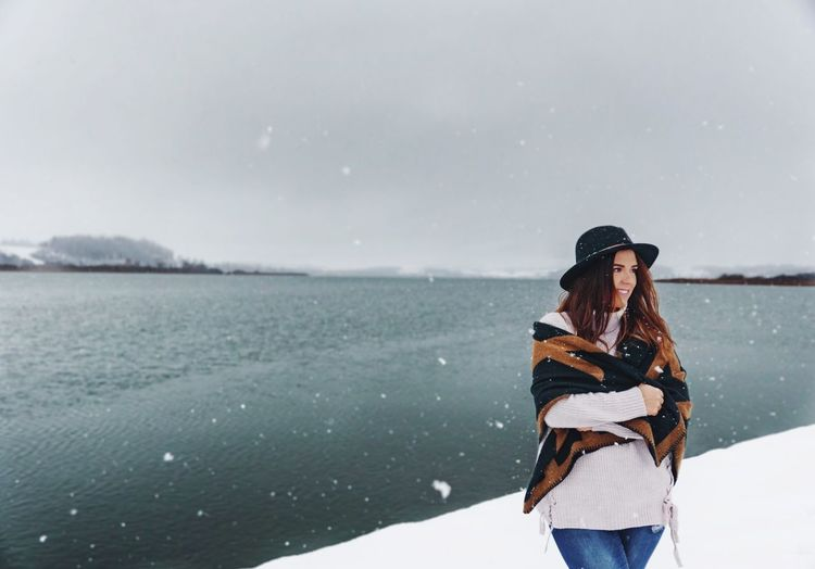 Smiling woman looking away while standing on snow covered shore against sky