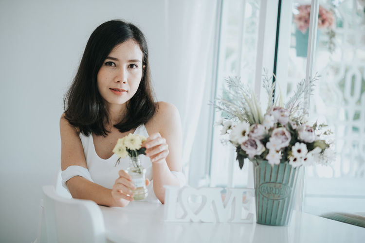 Portrait Of Woman Holding Flower At Table