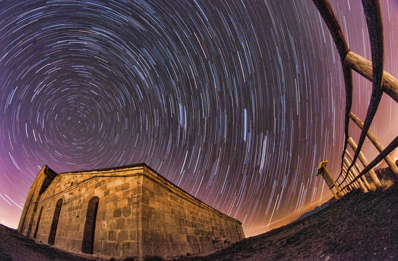 Low Angle View Of Built Structure Against Star Trail