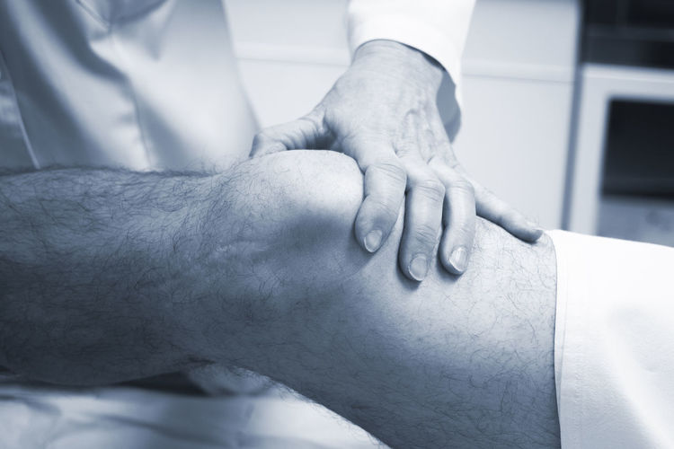Close-up of doctor examining patient knee in hospital