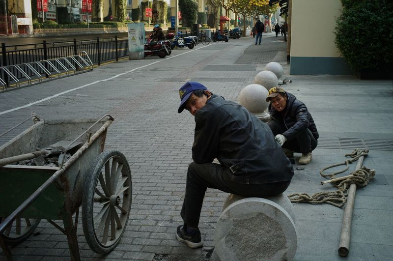 People sitting on road in city