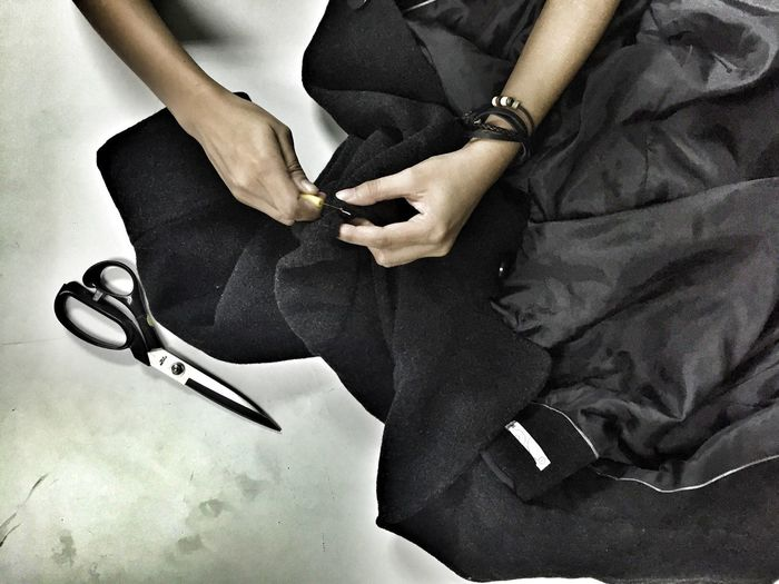 Cropped image of hands stitching jacket