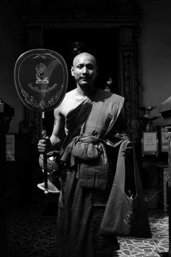 Portrait of monk holding award while standing in darkroom