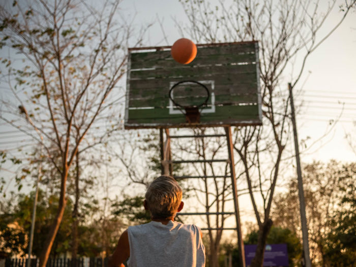 Rear view of senior man playing basketball at sunset
