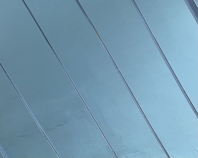 Low angle view of power lines against blue wall