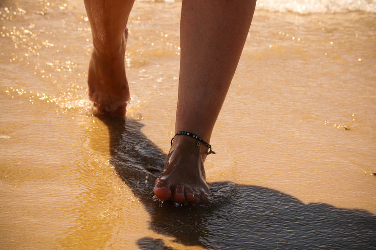 Low section of woman walking on beach in water