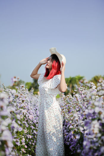 Woman wearing hat while standing amidst plants against clear sky