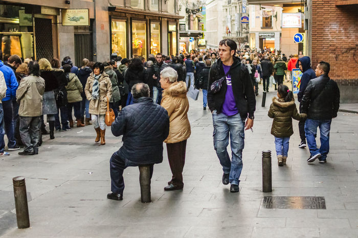 A man sitting on a short street bollard taking to his wife next to him in a street in Madrid. Casual Clothing City City Life Crowd Editorial  Editorialphotography Jeans Lifestyles Man Men People People Watching Queue Real People Sitting Sitting Standing Street Streetphotography Togetherness Women