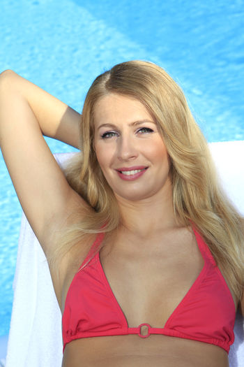 Portrait Of Smiling Woman Sitting On Lounge Chair At Poolside