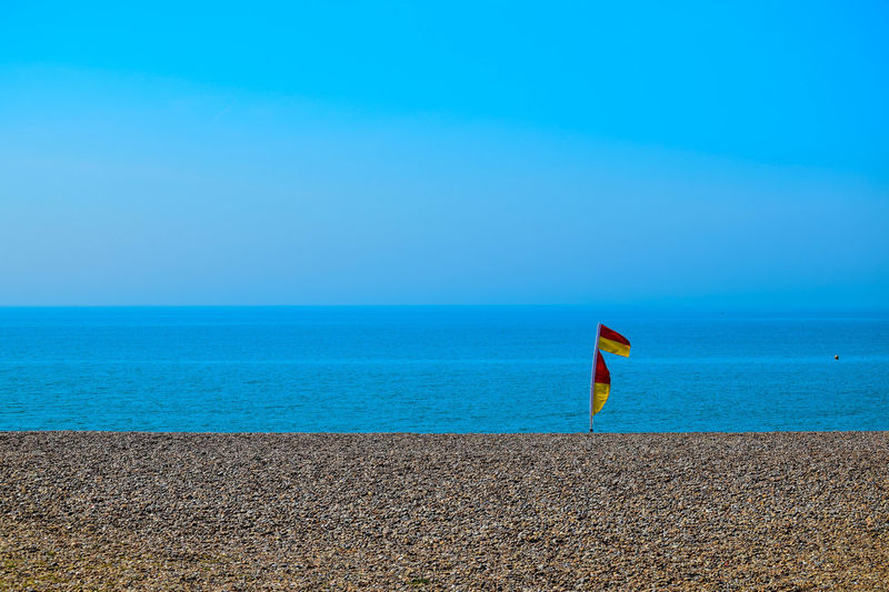 Beach Beauty In Nature Blue Clear Sky Day Flag Horizon Over Water Nature No People Outdoors Sand Scenics Sea Sky Space For Copy Summer Tranquil Scene Tranquility Vacations Water