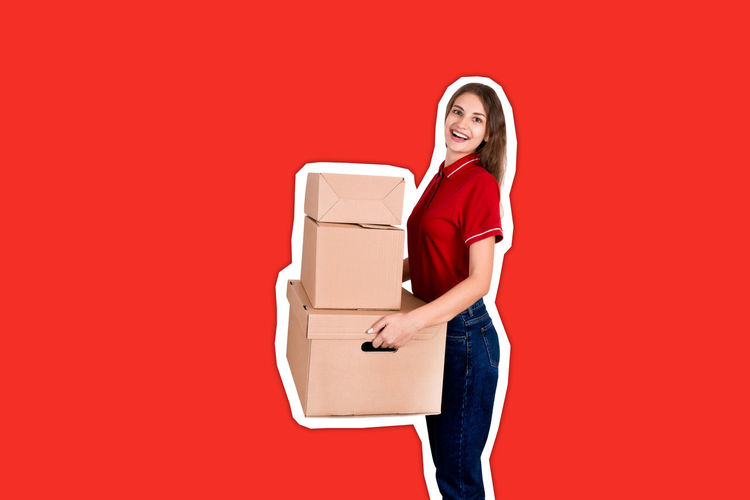 Portrait of a smiling young woman holding red box