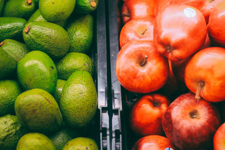 Apples and avocado at market for sale