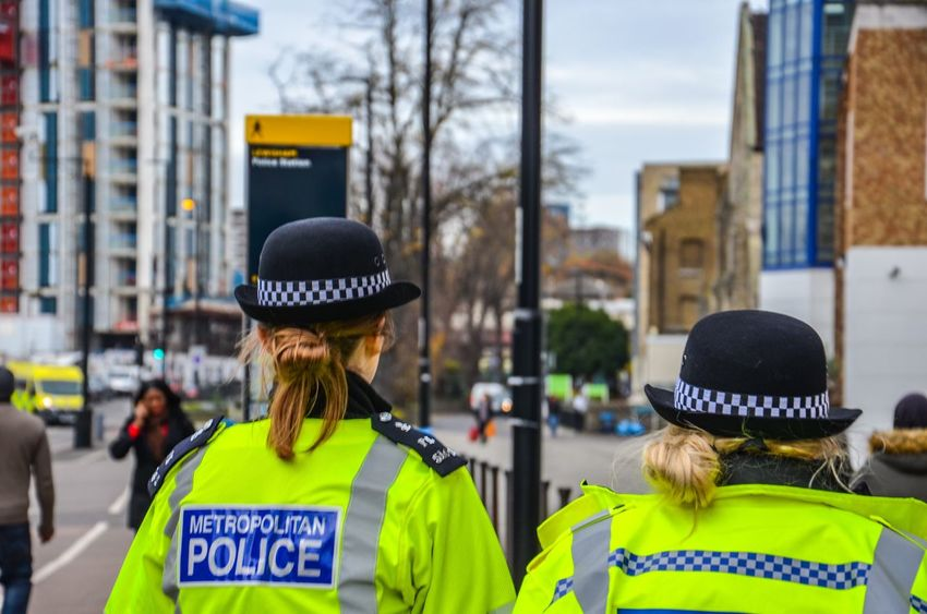 At Your Service Everyday Life Streets Of London Law Enforcers Security Law London Officers Metropolitan Police Bobby Bobbie Police Woman Police Text Rear View Safety Real People Jacket Reflective Clothing Protection Yellow Day Cap Outdoors City