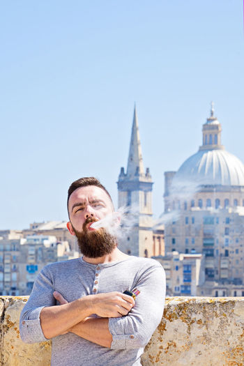 Architecture Building Exterior Built Structure One Person Beard Young Adult Facial Hair City Standing Building Sky Nature Smiling Young Men Copy Space Portrait Clear Sky Men Lifestyles Outdoors Vape Vaper Malta Summer Vacation Valletta Man Bearded Hipster - Person