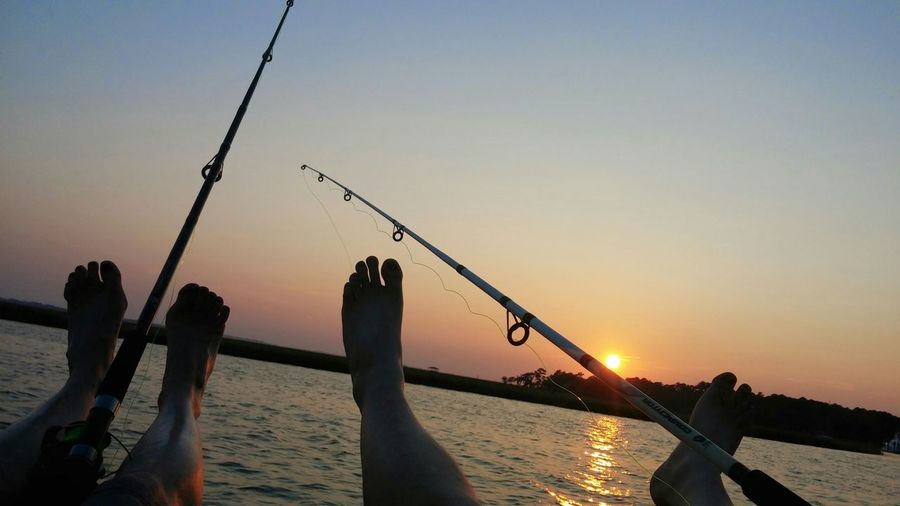 Low section of two people fishing in calm sea at sunset