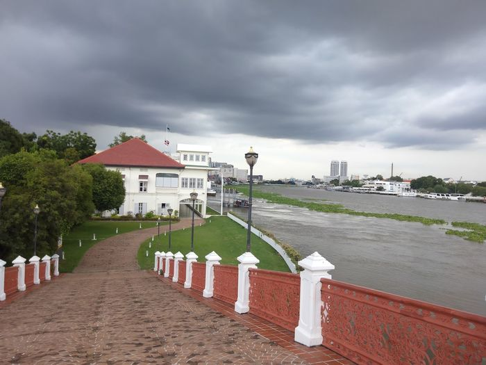 Footpath by river in city against sky