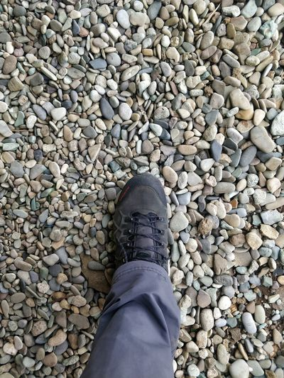 Low section of person standing on stones