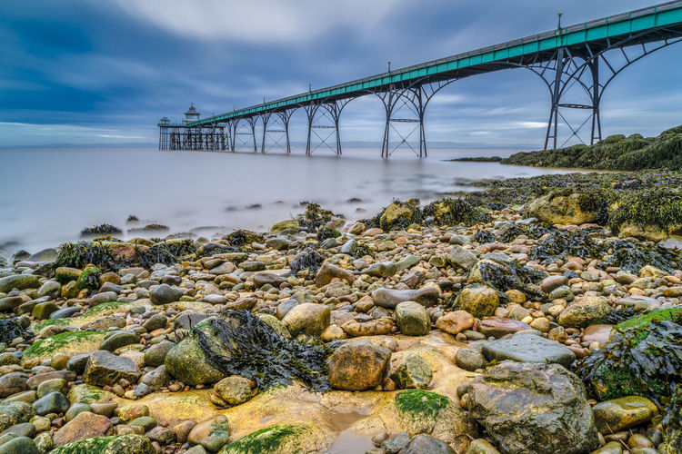 The Victorian Pier at Clevedon, Bristol, UK Water Bridge Bridge - Man Made Structure Connection Transportation Nature Architecture Built Structure Rock Solid Cloud - Sky Rock - Object No People Sky Beauty In Nature Sea Day Stone - Object Outdoors Pebble Bay Clevedon Pier Uk