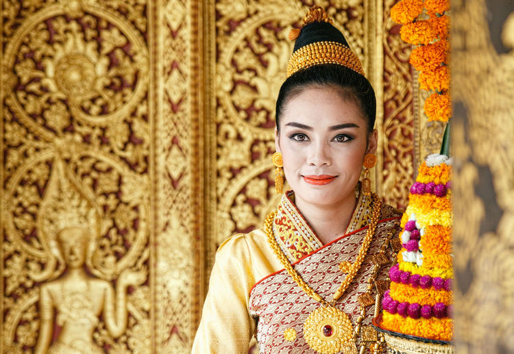 Portrait of smiling young woman wearing traditional clothing standing in temple