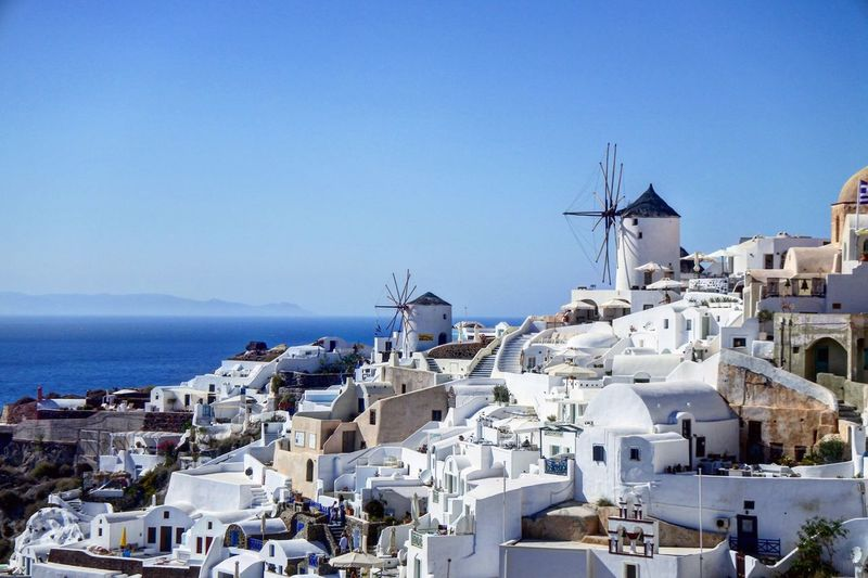 Houses At Santorini Island By Sea Against Clear Sky