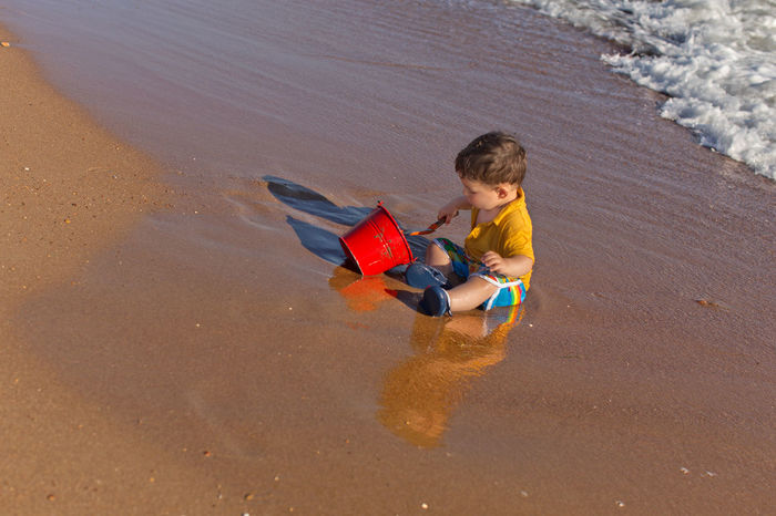 Toddler boy playing with red bucket at the beach Beach Boys Caucasian Ethnicity Child Childhood Concentration Cute Day Full Length Leisure Activity Lifestyles Outdoors People Real People Sand Sand Bucket Sand Shovel Side View Side Vieww Summer Taken From Above Toddler  Vacations Water Water Reflection