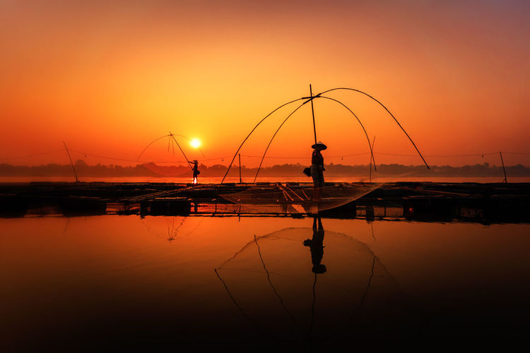 Silhouette fishing net on sea against sky during sunset