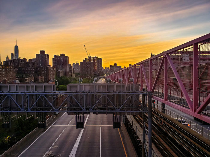 Bridge in city against sky during sunset