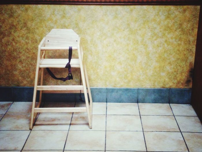 A child's high chair on it's own at the edge of the room. Furniture Wall Infant's Child's Wooden Emptiness Empty Tiled Floot Singular Alone High Chair No People Day