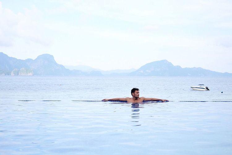 Man swimming in pool against sea