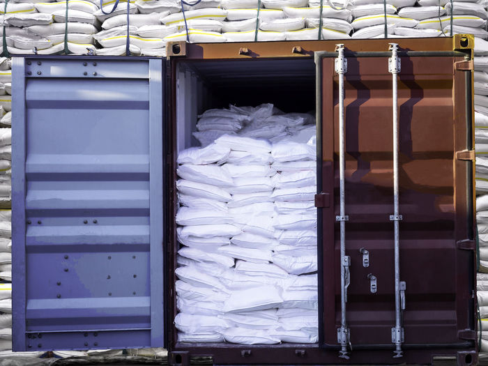 Sugar in bags are stuffing in container for export. Container Industry Rice Sugar Thailand Business Day Equipment Export Flour Freight Full Frame Handling Indoors  Labor Loading Port Portrait Shipping  Stack Starch Storm Cloud Stuffing Tapioca Trade