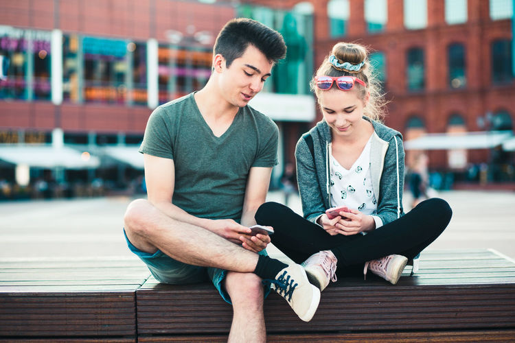 Young couple sitting on bridge in city
