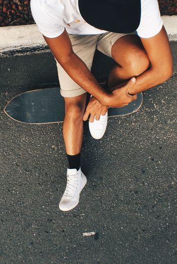 High angle view of man sitting with skateboard on street