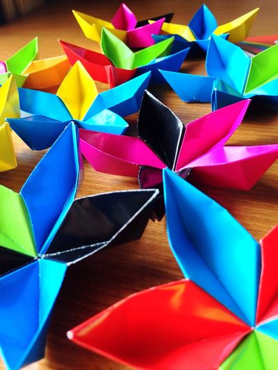Colorful paper flowers on table at home