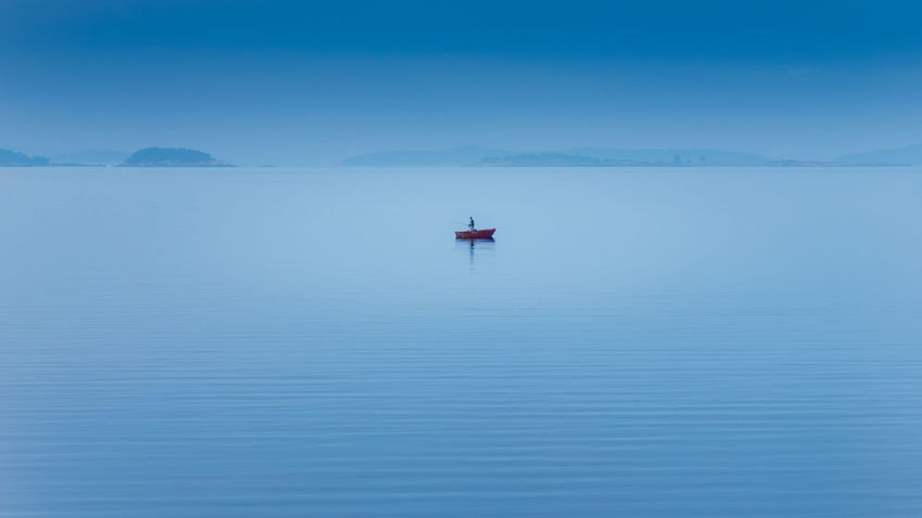 an angler in a boat on a lake in norway Angler Morning Morning Light Morning Sky Beauty In Nature Blue Boat Clear Sky Horizon Over Water Lake Lakeside Nature Outdoors People person Reflection Scenics Sea Sky Tranquil Scene Tranquility Water Waterfront