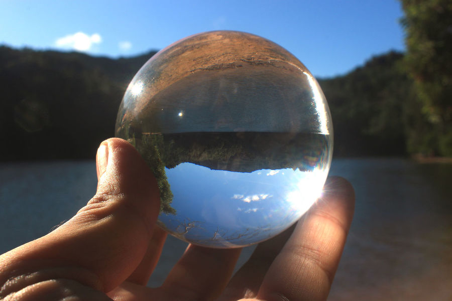 Crystal Ball Reflection Bubble Human Body Part Fortune Telling Close-up Holding Eyesight Refraction Fragility Planet Earth Outdoors Sky Day Water People Reflections Glass Ball Focus On Foreground Nature Barragem Da Mula Sintra Portugal Glass Tranquility