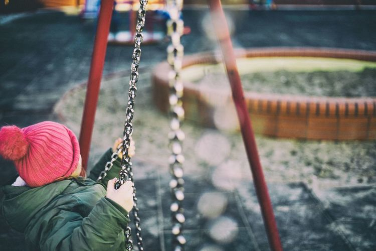 Rear view of boy on swing in playground
